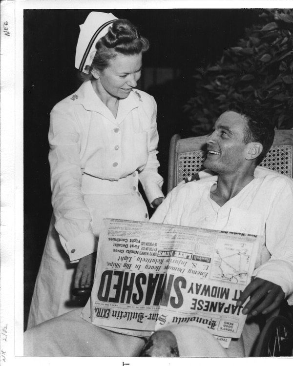 Ensign George H. Gay at Pearl Harbor Naval Hospital, with a nurse and a copy of the Honolulu Star-Bulletin newspaper featuring accounts of the battle. (National Archives)