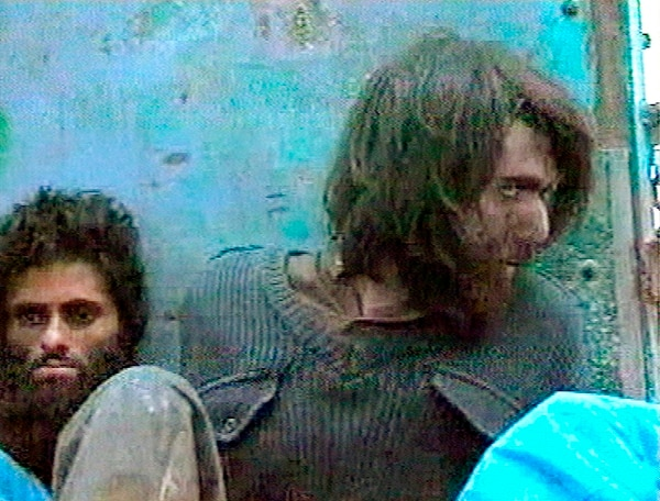This file image taken Dec. 1, 2001, from television footage in Mazar-i-Sharif, Afghanistan, shows John Walker Lindh, right, claiming to be an American Taliban volunteer. (AP Video, File)