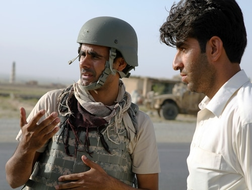 An Afghan interpreter translates to an Afghan local national during a Entry Control Point stop in Qarabagh, Afghanistan, Aug. 24, 2013. Interpreters are able to apply for special visas to immigrate to the U.S., but the process is arduous. (Spc. Ryan D. Green/Army)