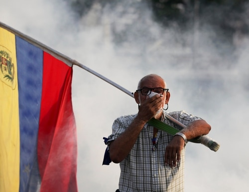 An opponent to Venezuelan President Nicolas Maduro carrying a Venezuelan flag covers his face amid tear gas fired by soldiers loyal to Maduro during an attempted military uprising to oust Maduro in Caracas, Venezuela, Tuesday, April 30, 2019. (Boris Vergara/AP)