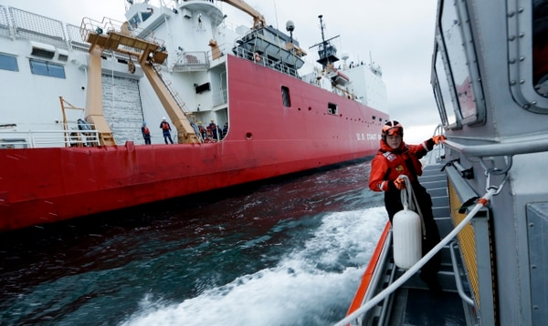 A small U.S. Coast Guard boat pulls alongside the cutter Healy to drop off passengers as the icebreaker makes its way through the Puget Sound after cutting its way to the North Pole in support of a mission to study the health of the Arctic Ocean. (Elaine Thompson/AP)