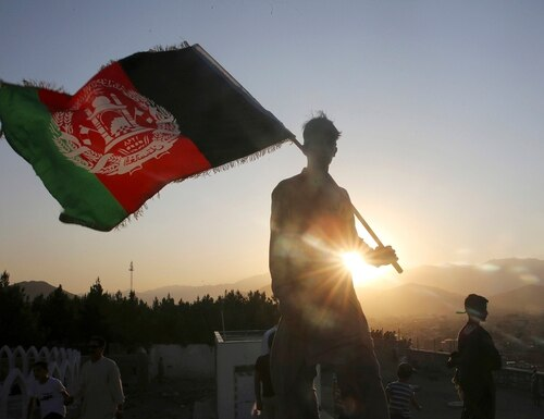 In this Aug. 19, 2019, file photo, a man waves an Afghan national flag during Independence Day celebrations in Kabul, Afghanistan. (Rafiq Maqbool/AP)