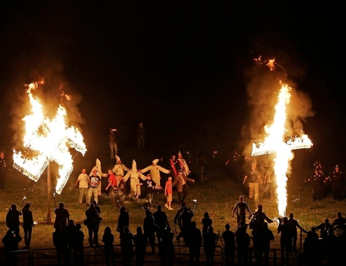 Members of the Ku Klux Klan participate in cross and swastika burnings after a