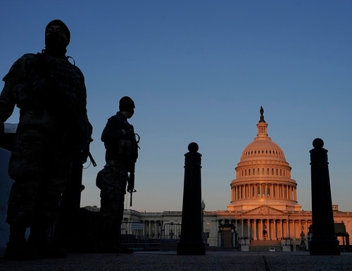 National Guard stand their posts around the Capitol at sunrise in Washington, March 8, 2021. (Carolyn Kaster/AP)