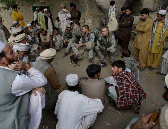 Lt. Thomas Goodman, center, meets with villagers in Qatar Kala in the Pech Valley of Afghanistan's Kunar province with his interpreter Ayazudin Hilal, center left with hat. (AP Photo/David Guttenfelder, File)